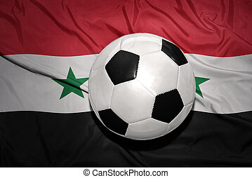 black and white football ball on the national flag of syria...