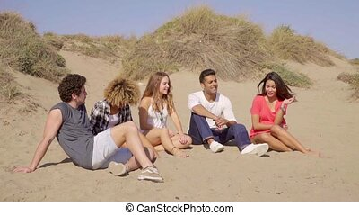 Young People Sitting On The Beach - Five young friends...