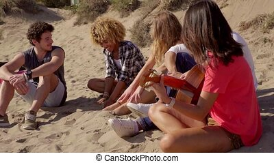 Group of young friends chilling out at the seaside sitting...