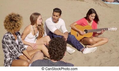 Young friends chilling out on a sandy beach - Multiracial...