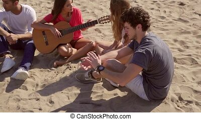 Young friends relaxing on a beach playing guitar - Young...