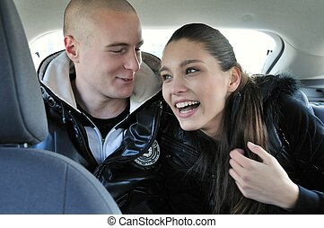 Young couple having fun in car - Young couple dressed in...