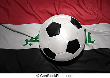 black and white football ball on the national flag of iraq -...