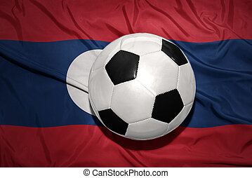 black and white football ball on the national flag of laos -...