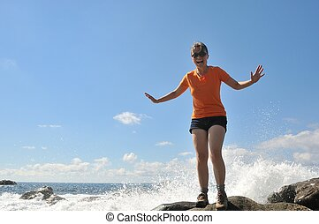 Young woman splashed by sea wave