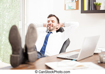 Businessman relaxing in his office - Happy businessman with...