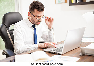 Businessman with eye fatigue working in an office - Portrait...