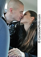 Intimate moments - couple in car - Young couple kissing on...
