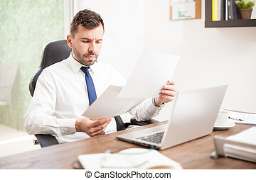 Businessman reviewing some charts - Busy young businessman...