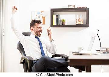 Businessman getting great news on the phone - Profile view...