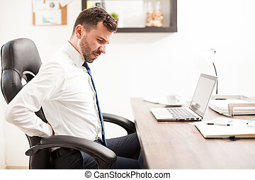 Businessman with back pain in the office