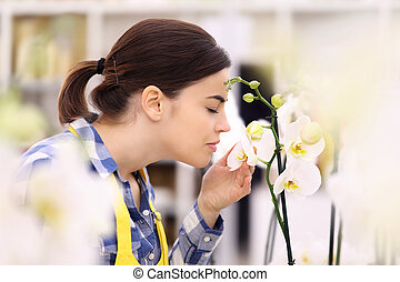 woman touches and smells an orchid