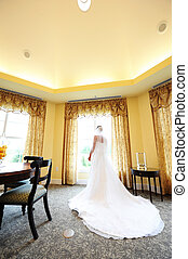 wedding day - bride is in the waiting room with looking out...