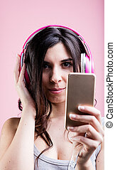 woman listening to music using a smartphone and her pink...