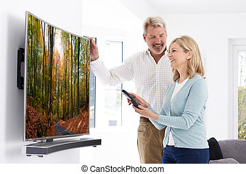 Mature Couple With New Curved Screen Television At Home