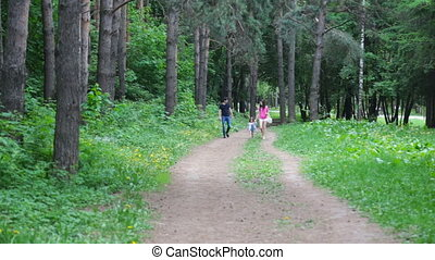 Mom and young daughter and dad, a young family on a walk in the park in summer