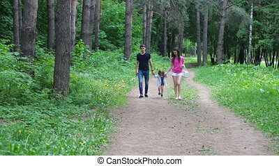 Mom and young daughter and dad, a young family on a walk in...