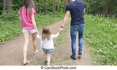 cute baby girl walking in park with parents summer