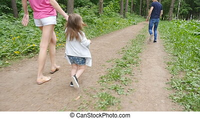 cute baby girl walking in park with parents