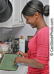 Doing the Dishes - A young black woman doing the dishes