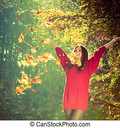 Girl tossing up leaves Young woman in autumnal forest...