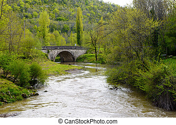 River with an old bridge in the mountains - a river with an...