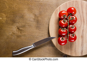 Tomato branch on vintage wood table - Red tomato branch on...