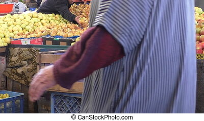 Morocco market fruit stall apples - Fruit seller wearing...