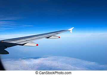 Wing of a Plane with Blue Sky and Clouds