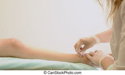 Closeup of female therapist waxing customer's leg at beauty...