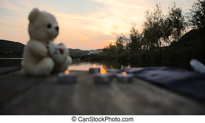 Candles and bear on the lake dock