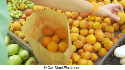 Woman choosing ripe apricots on the market