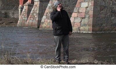 Man talking on smart phone near river
