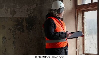 Building inspector with documentation in room near window