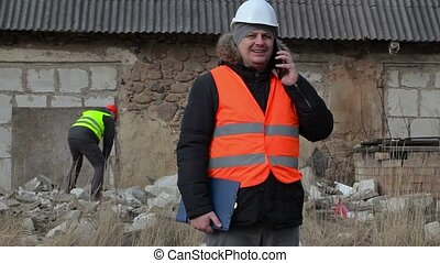 Building inspector talking on smartphone in background...