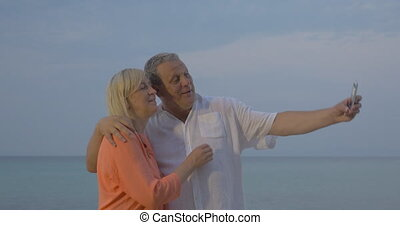 Senior couple making vacation selfie on mobile - Cheerful...
