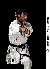 High Contrast karate young male fighter on black background