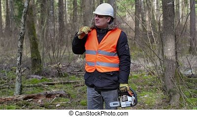 Lumberjack with chainsaw and ax walking away in forest