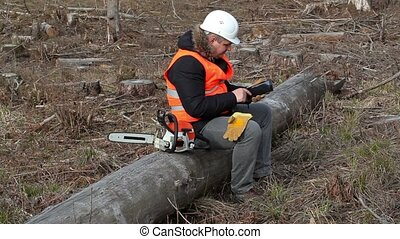Lumberjack with chainsaw sitting on tree and using tablet PC
