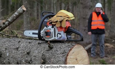 Chainsaw with gloves in background lumberjack talking on...