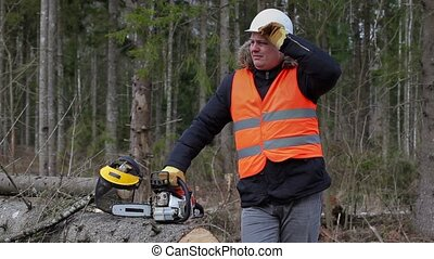 Tired lumberjack near chainsaw in forest