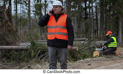 Forest Officer with smartphone and worker start fixing...