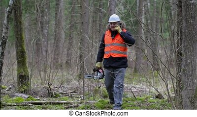 Lumberjack with chainsaw and smart phone in forest