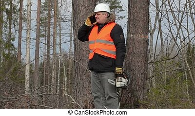 Lumberjack with chainsaw talking on smart phone near tree