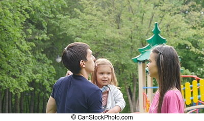 Young parents kissing their daughter