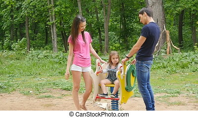 playful child with parents at the playground outdoor. Mom,...