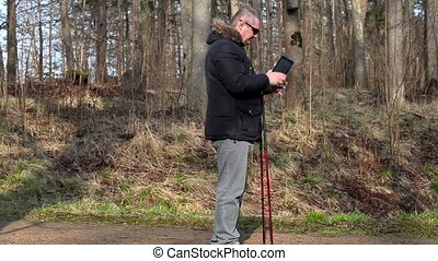 Hiker with walking sticks take pictures on tablet PC