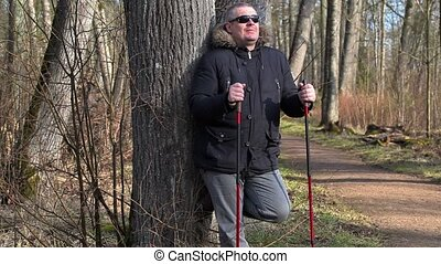 Hiker with walking sticks enjoy nature in park