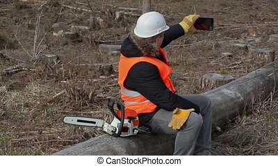 Lumberjack sitting on tree near chainsaw and using tablet PC