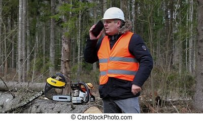Lumberjack talking on cell phone near chainsaw in forest